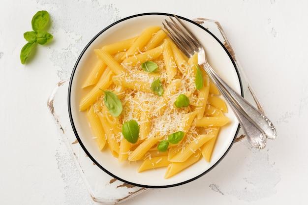 Penne rigate pasta con parmigiano e foglie di basilico in un piatto di ceramica sulla vecchia tavola di cemento leggero.
