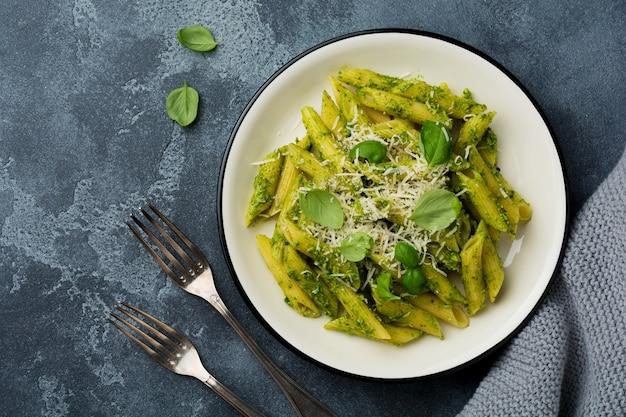 Penne rigate pasta con parmigiano e foglie di basilico in piatto di ceramica sul vecchio tavolo in cemento grigio vintage.