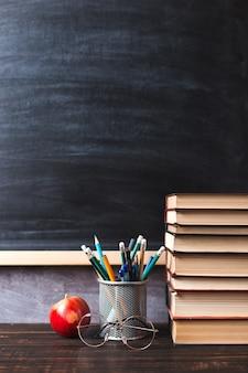 Penne, mele, matite, libri e bicchieri sul tavolo, sullo sfondo di una lavagna