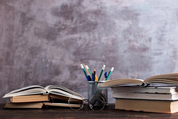 Penne, mele, matite, libri e bicchieri sul tavolo