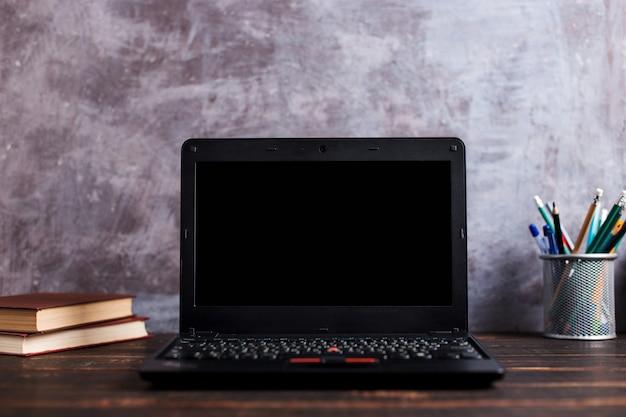 Penne, mela, matite, libri, laptop e bicchieri sul tavolo, su sfondo lavagna