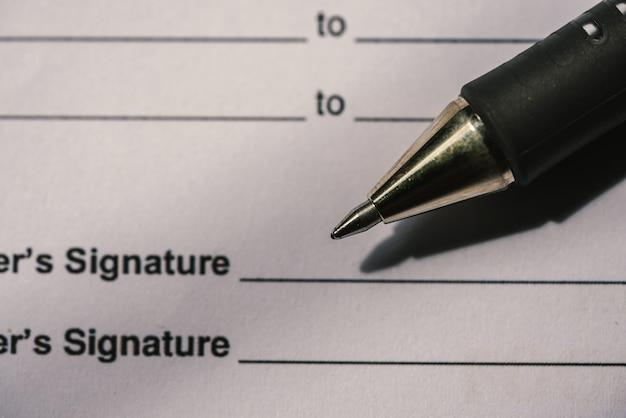 Penne e documenti contrattuali sono posti sulla scrivania.