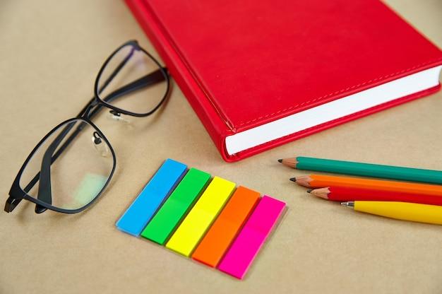 Penne, penne, matite, bicchieri, segnalibri, su uno sfondo di carta, close-up