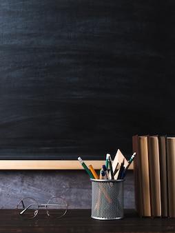 Penne, matite, libri e bicchieri sul tavolo, sullo sfondo della lavagna