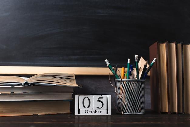 Penne, matite, libri e bicchieri sul tavolo, sullo sfondo della lavagna. calendario 5 ottobre, copia dello spazio.