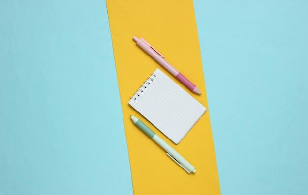 Penne con il primo piano del taccuino su fondo giallo blu
