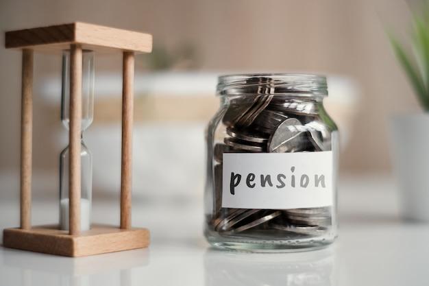 Concetto di risparmio di pensione - vaso di vetro con monete e iscrizione.