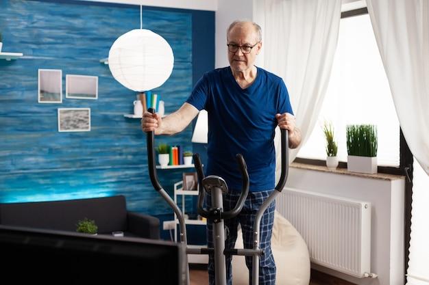 Il pensionato che fa le gambe esercita l'allenamento muscolare del corpo utilizzando la macchina per biciclette durante il lavoro di aerobica ...