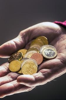 Uomo del pensionato che tiene nelle mani le monete in euro. tema delle pensioni basse.
