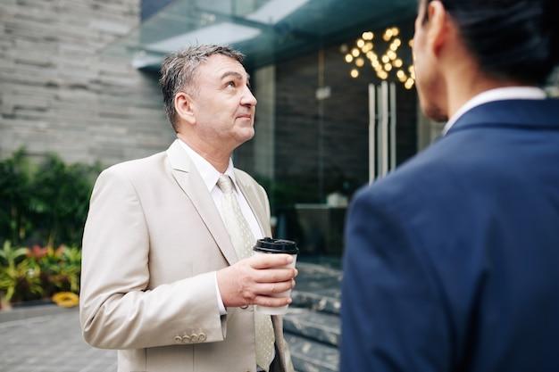 Imprenditore invecchiato pensieroso che beve il caffè del mattino con il suo collega e guarda l'edificio per uffici in cui stanno lavorando