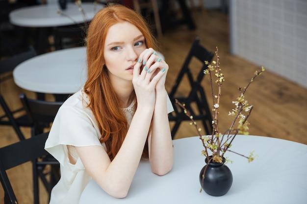 Giovane donna attraente pensierosa con capelli rossi lunghi che si siede alla tavola in caffè