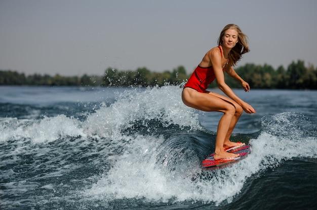 Ragazza bionda pensierosa che guida sul wakeboard rosso