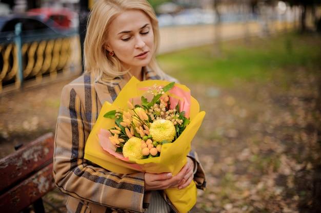 Donna bionda pensierosa in cappotto plaid seduto sulla panchina con un mazzo di fiori gialli