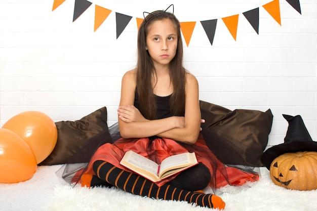 Ragazza bruna pensierosa in costume da strega con libro di stregoneria che celebra halloween a casa