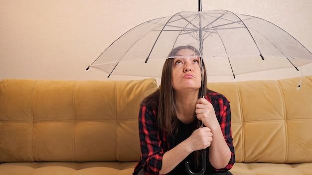La donna castana pensierosa in camicia a quadretti si nasconde dall'acqua che scorre dai vicini di sopra sotto l'ombrello trasparente che si siede sul sofà nella stanza