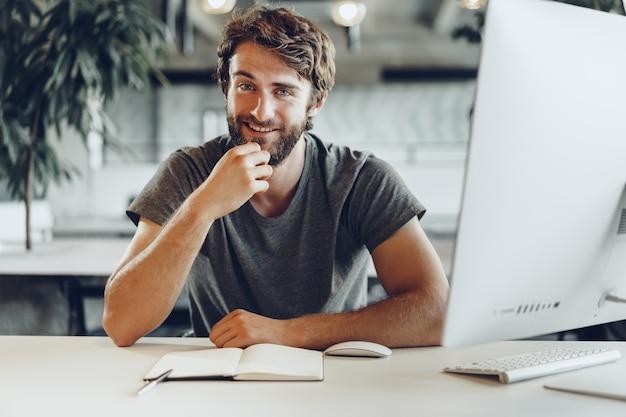 Uomo d'affari pensieroso seduto al suo tavolo di lavoro in un ufficio