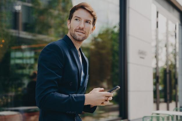 L'uomo d'affari pensieroso tiene il cellulare invia messaggi di testo vestiti in modo formale