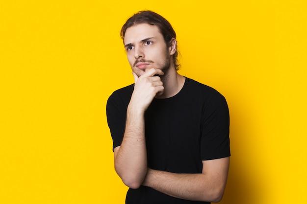 L'uomo caucasico pensieroso in camicia nera sta toccando il mento pensando a qualcosa