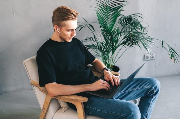 Il programmatore mobile dello sviluppatore dell'uomo caucasico pensieroso scrive il codice del programma su un computer portatile nell'ufficio domestico.