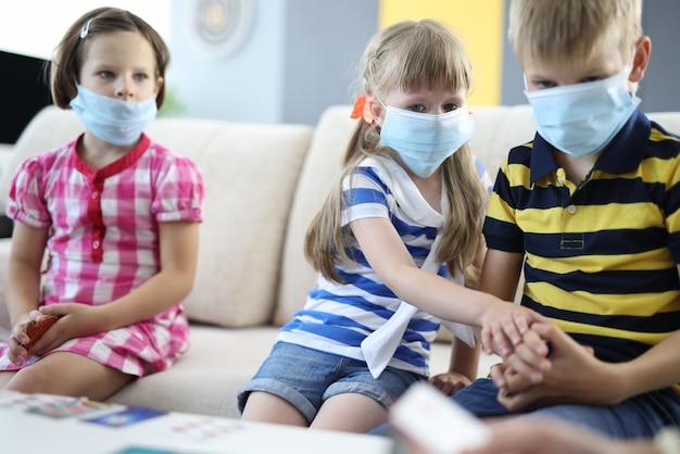 I bambini pensierosi sono seduti sul divano indossando maschere mediche protettive e tenendo carte da gioco da tavolo