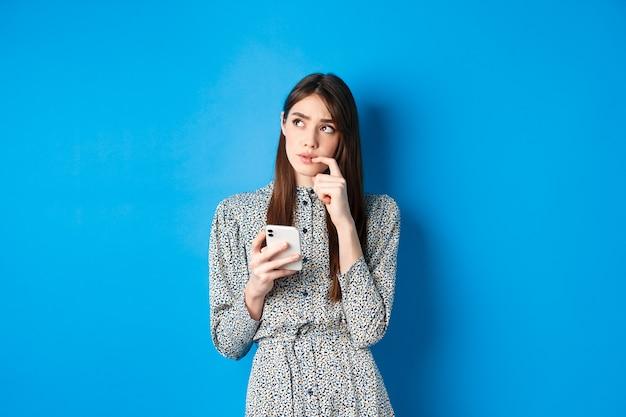 Ragazza carina pensierosa pensando a come rispondere al messaggio, guardando da parte premuroso e tenendo lo smartphone, in piedi in abito blu.