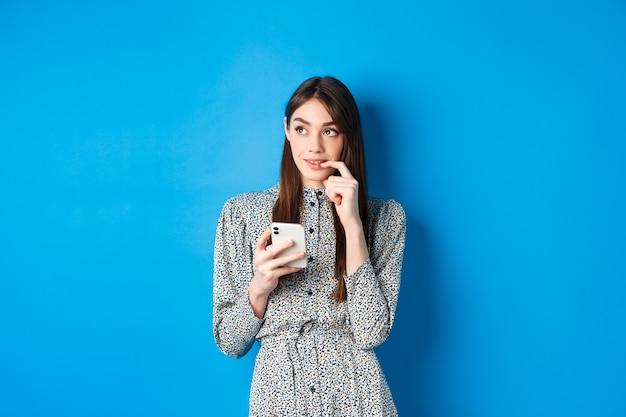 Donna carina pensierosa pensando a come rispondere al messaggio, guardando da parte premuroso e tenendo lo smartphone, in piedi in abito blu.