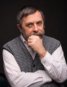 Uomo anziano pensieroso che propone nello studio su uno sfondo scuro
