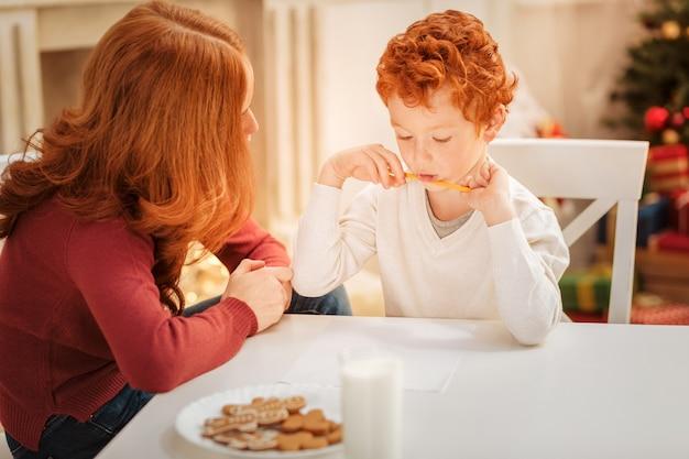 Famiglia pensierosa che si riunisce a un tavolo da pranzo mentre fa un elenco di regali di natale e scrive una lettera a babbo natale.