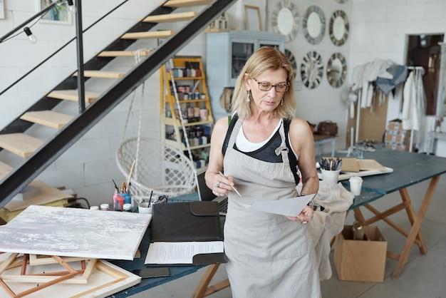 Pensieroso artista femminile in grembiule e occhiali da vista guardando schizzo mentre si lavora su una nuova foto in studio