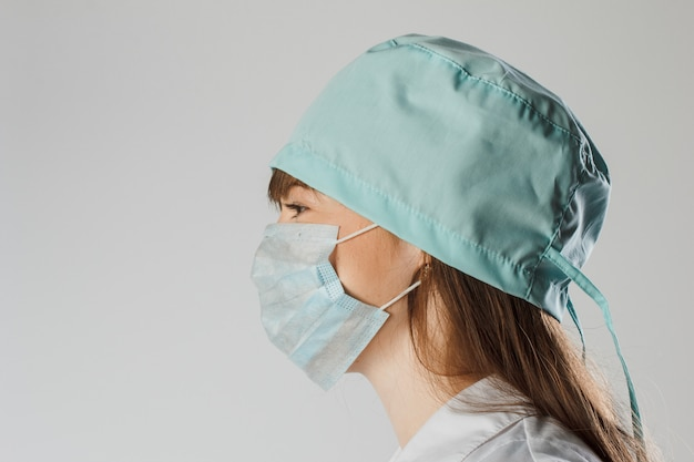 Medico o infermiere femminile pensieroso che indossa maschera e cappuccio protettivi