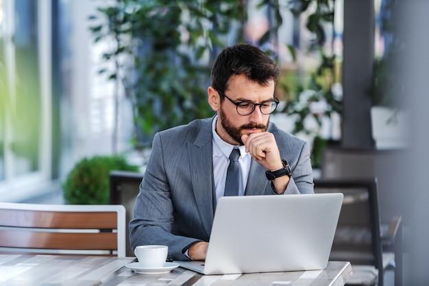 Uomo d'affari barbuto caucasico concentrato pensieroso in vestito con gli occhiali che si siede sulla terrazza del caffè e utilizzando il computer portatile.