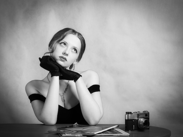 Ragazza pensierosa in abito da sera seduta a tavola con riviste