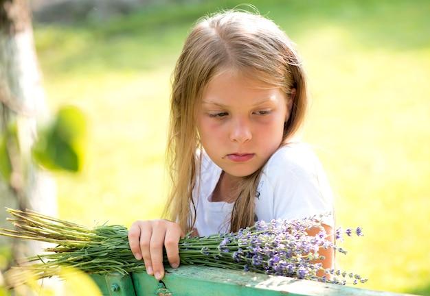 Una ragazza pensierosa si siede su una panchina con un mazzo di fiori vicino a una casa privata