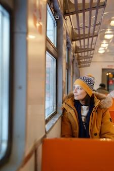Ragazza pensierosa che viaggia in treno locale nel periodo invernale, guardando attraverso la finestra al paesaggio innevato