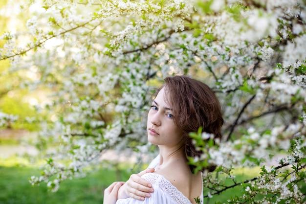 Ragazza pensierosa in una giacca bianca su uno sfondo di alberi in fiore