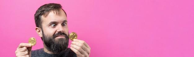 Un ragazzo pensieroso con la barba su uno sfondo rosa pensando all'espressione pensierosa della domanda