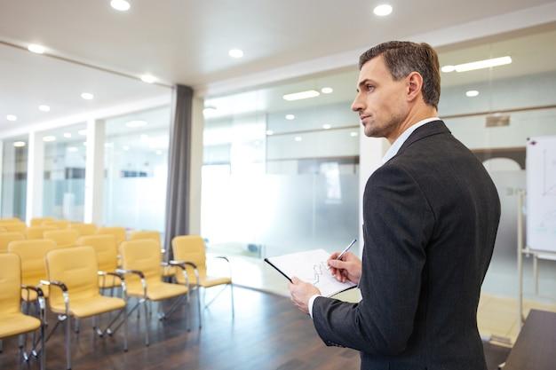 Uomo d'affari bello pensieroso con appunti in piedi nella sala conferenze vuota empty