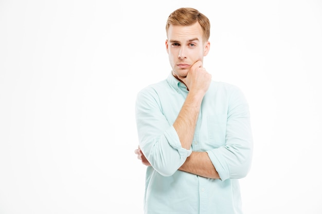 Bel giovane uomo d'affari pensieroso che sta con le mani piegate e pensa al muro bianco white