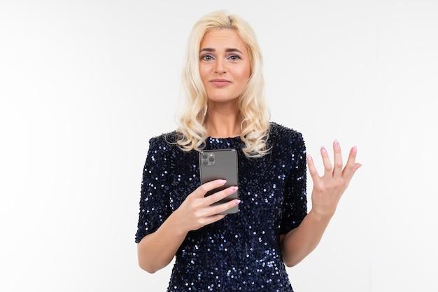 Signora pensierosa in un abito lucido navigare in internet dal telefono su uno sfondo bianco con spazio di copia