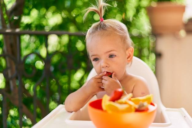 La bambina pensierosa si siede su un seggiolone e mangia la fragola