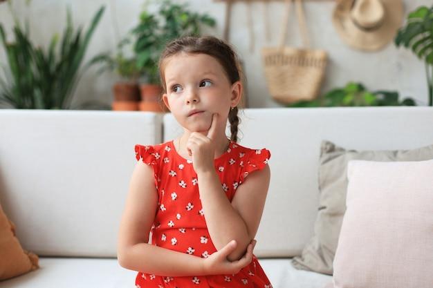 Bambina pensierosa che si siede sul divano in soggiorno. sognare ad occhi aperti.