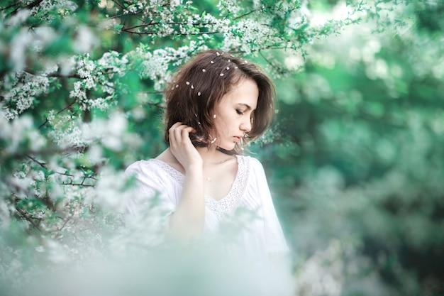 Ragazza adorabile pensierosa su un fondo degli alberi di fioritura.