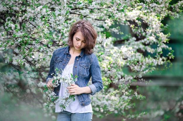 Ragazza adorabile pensierosa dell'apparenza europea su un fondo degli alberi di fioritura.