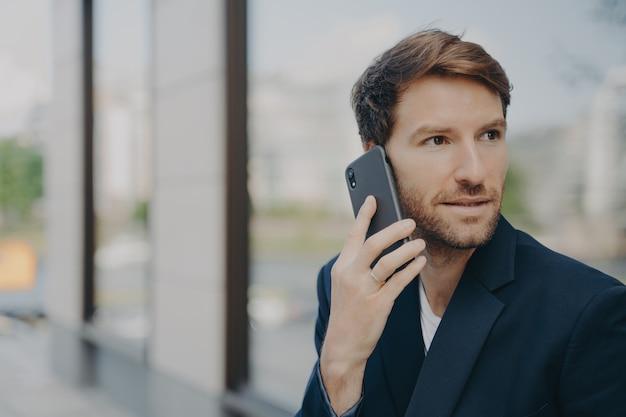 Imprenditore maschio pensieroso focalizzato sulla distanza fa rispondere alle chiamate usando il telefono cellulare