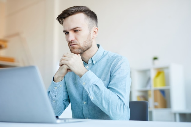 Uomo pensieroso con laptop