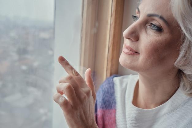 Pensieroso donna matura bere tè e guardare fuori dalla finestra, blocco e concetto di isolamento, fuoco selettivo