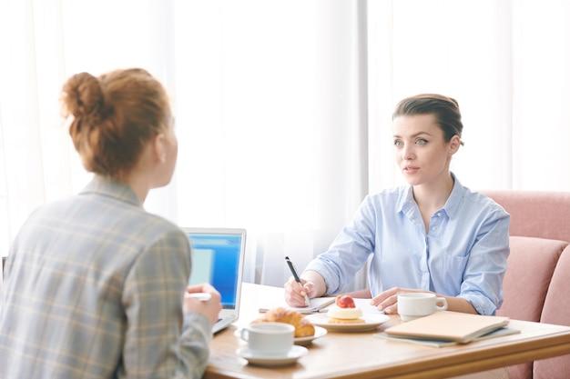 Pensierose donne d'affari moderne sedute a tavola con tazze di caffè e dessert e discutendo l'attuazione del progetto durante il pranzo
