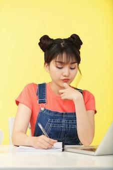 Piuttosto giovane donna pensierosa che scrive nel quaderno quando fa i compiti di matematica e risolve le equazioni