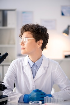 Virologo pensieroso propositivo dai capelli ricci in camice da laboratorio e guanti seduto alla scrivania in laboratorio moderno e distogliere lo sguardo