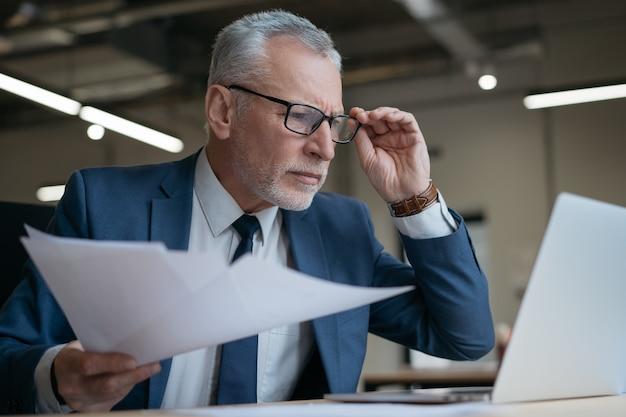 Imprenditore senior pensieroso utilizzando il contratto di lettura del computer portatile, cercando in linea